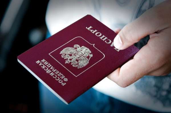Человек держит в руке российский паспорт