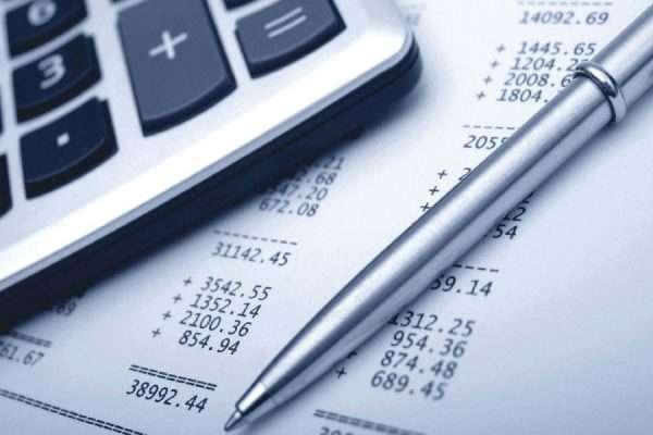 Фрагмент калькулятора и авторучка на фоне бумаги с цифрами