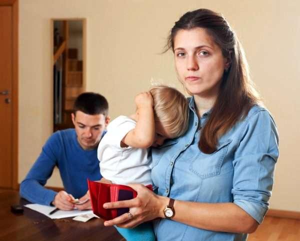 Женщина держит ребёнка, на заднем плане — мужчина с деньгами в руках