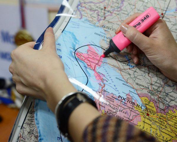 Человек выделяет Крым на карте маркером