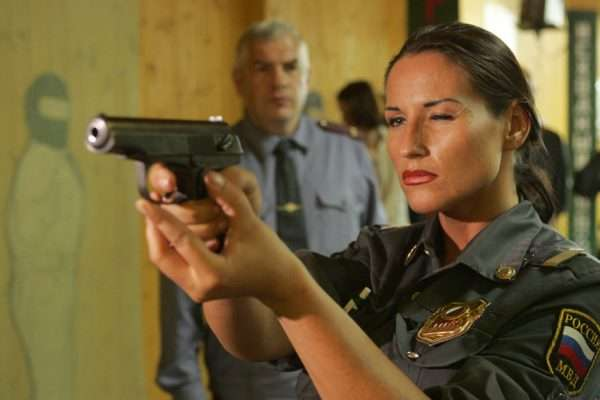 Женщина-полицейский целится из пистолета