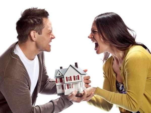 Мужчина и женщина перетягивают игрушечный домик