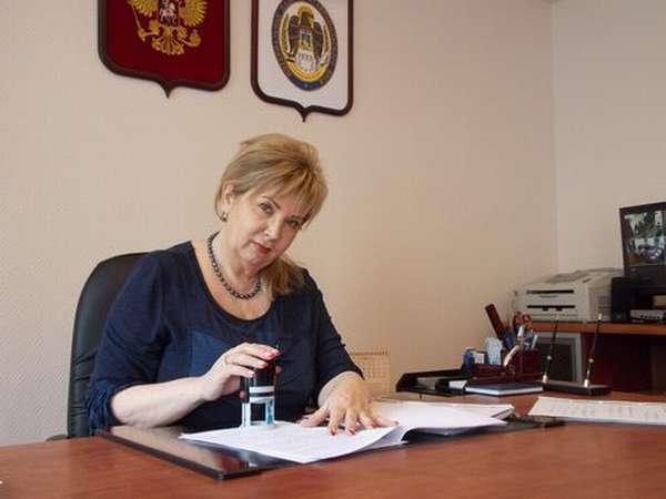 Женщина ставит печать на документ