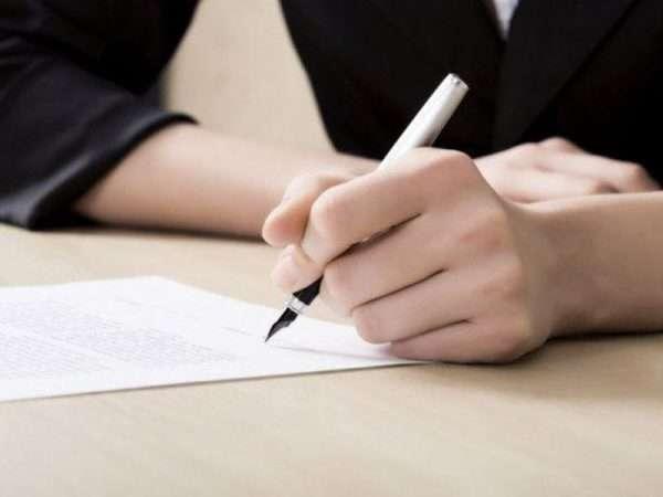 Руки подписывающей документ женщины