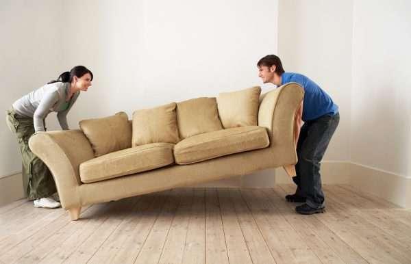 Женщина и мужчина поднимают диван