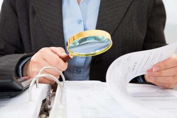 Мужчина рассматривает папку с бумагами через лупу