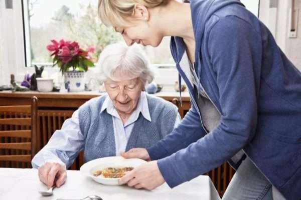 Девушка подаёт суп пожилой женщине