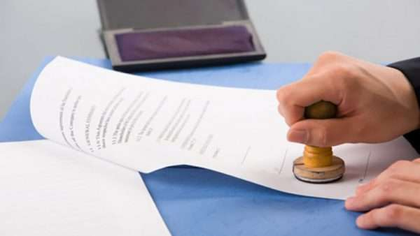 Рука ставит печать на документ
