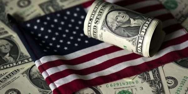 Доллары США на фоне американского флага