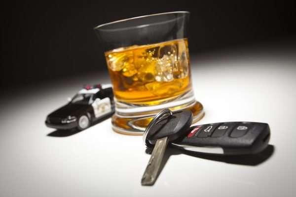 Стакан алкоголя, ключи от машины и патрульный автомобиль