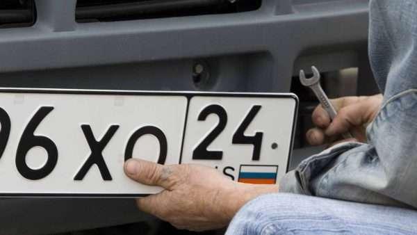 Мужчина снимает номера с машины