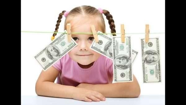 Маленькая девочка смотрит на денежные купюры