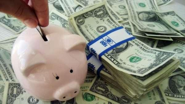 Свинья-копилка, в которую опускают монетку, и денежные купюры