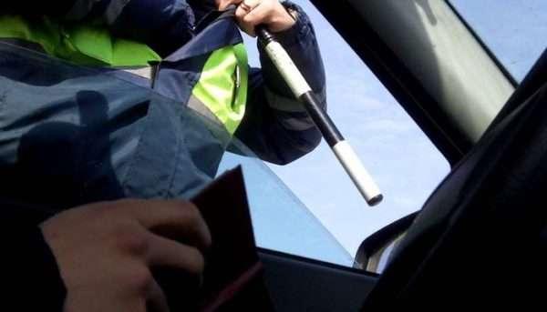 Водитель протягивает документы инспектору ГИБДД