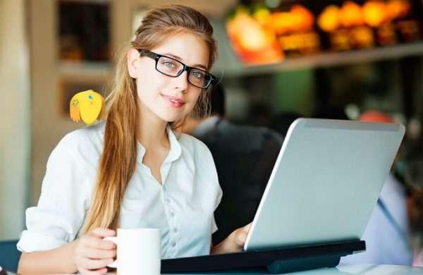 Девушка с чашкой в руке работает за ноутбуком