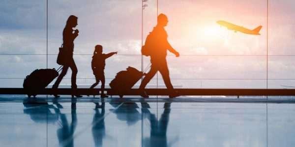 Семья в аэропорту на фоне взлетающего самолёта