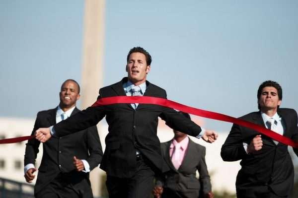 Мужчина в официальном костюме финиширует, срывая красную финишную ленточку