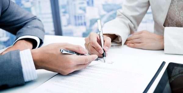Два человека подписывают документ