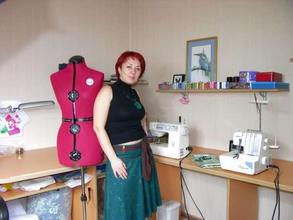 Девушка, занимающаяся пошивом одежды на дому, возле своего рабочего места