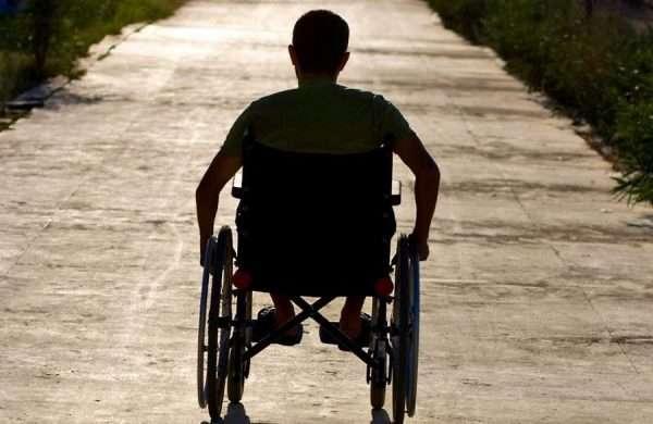 Человек в инвалидной коляске на дороге