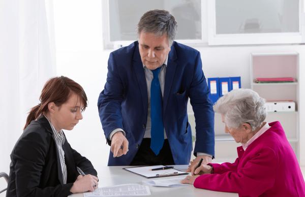 Пожилая и молодая женщины за столом в процессе оформления документов и мужчина, поясняющий процедуру