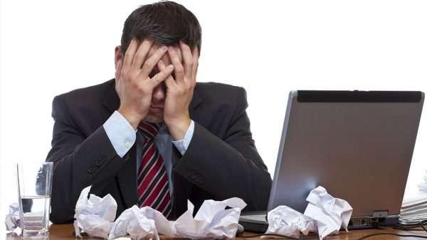 Мужчина закрывает лицо руками, сидя за рабочим столом