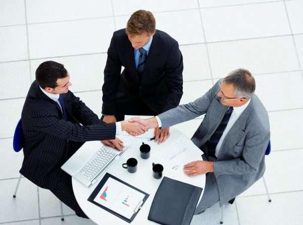 Пожимающие друг другу руки мужчины за круглым столом