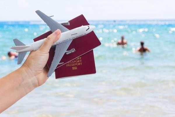 Рука с паспортами и самолётом на фоне моря