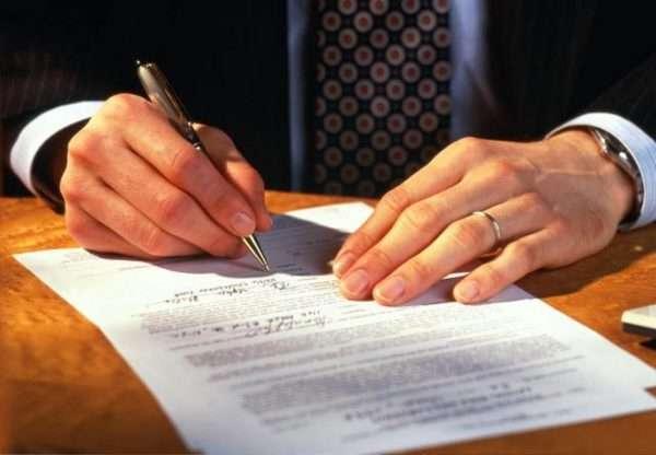 Мужчина подписывает договор