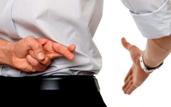 Мужчина протягивает руку, скрестив на другой руке пальцы