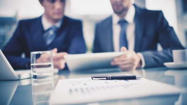 Мужчины в деловых костюмах за столом с документами