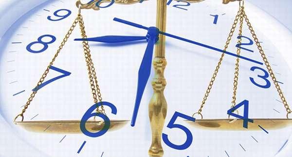 Весы на фоне часов