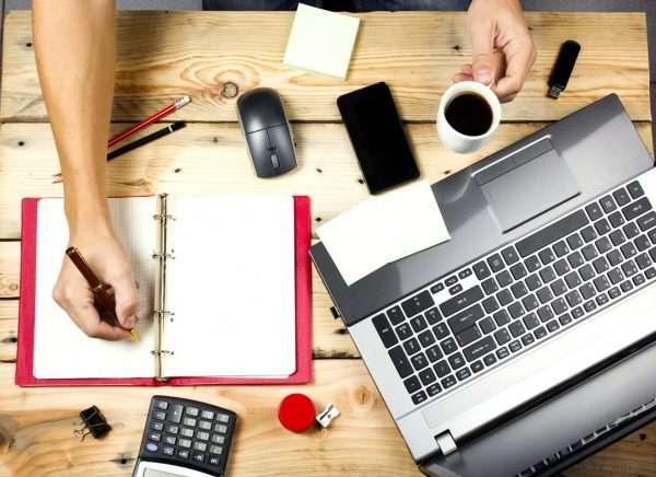 Ноутбук, блокнот, кружка кофе и другие атрибуты бизнеса