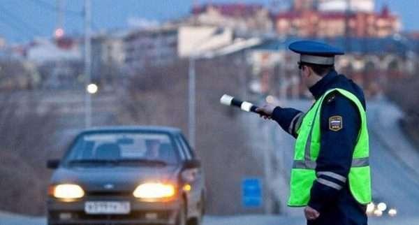 Инспектор ГИБДД останавливает атомобиль