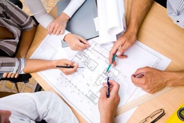 Руки нескольких людей правят карандашами и ручками план жилья