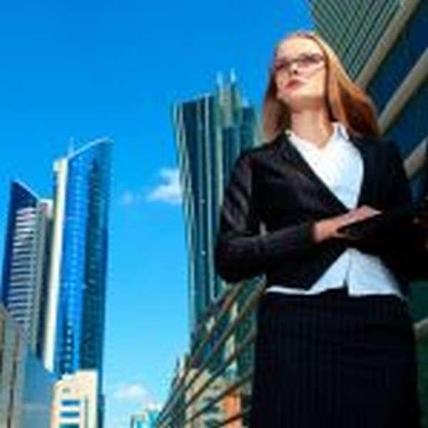 Женщина в костюме и с ноутбуком в мегаполисе