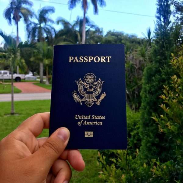 Паспорт гражданина США в руке на фоне парка