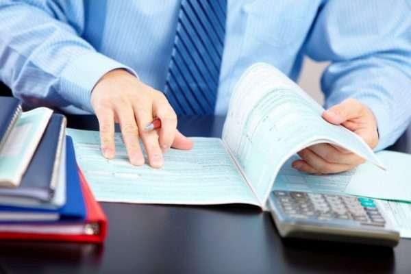 Мужчина с ручкой держит открытый документ