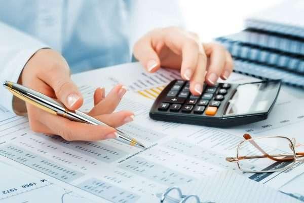 Таблицы на бумаге, калькулятор и ручка в руках