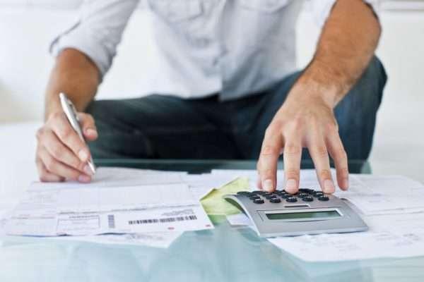 Мужчина с калькулятором заполняет документы