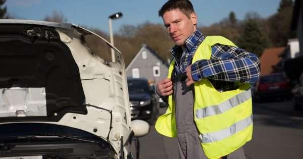 Мужчина в светоотражающем жилете рядом с багажником автомобиля