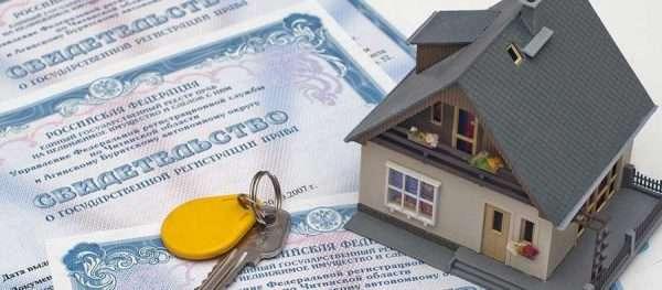 Домик и ключи на фоне свидетельств о госрегистрации