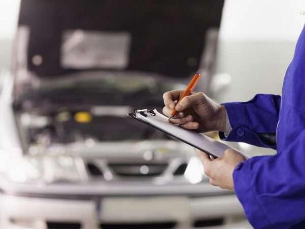 Технический эксперт делает записи около автомобиля
