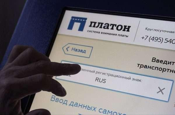 Рука на экране системы оплаты «Платон»