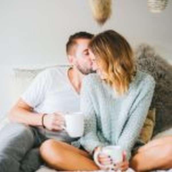 Влюблённая пара с чашками на кровати