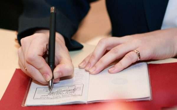 Женщина вносит сведения о регистрации в паспорт