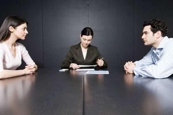 Мужчина и женщина сидят напротив друг друга в присутствии третьей стороны, оформляющей документы
