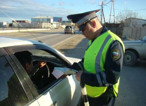 Сотрудник ДПС смотрит документы водителя